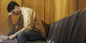 Stressed man sitting in waiting room